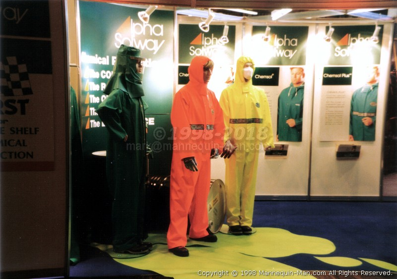 Wearing a High Visibility (Hi-Vis) Orange Chemsol Plus Chemical protective clothing coverall suit standing with two real mannequins. Living Mannequin stands between actual mannequins