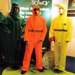 mannequin-man performming as a Living and Real Mannequin: Wearing a High Visibility (Hi-Vis) Orange Chemsol Plus Chemical protective clothing coverall suit and hard hat, standing between two real mannequins, one wearing a Saturn Yellow Chemsol Plus coverall and the other a green Chemmaster suit. for Alpha Solway on 17/09/1998