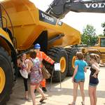 mannequin-man performming as a Living and Real Mannequin: Living Mannequin man standing by an A40F digger scaring empoyees and family members at the volvo employee family day at the office in Duxford for Volvo Trucks on 03/07/2011