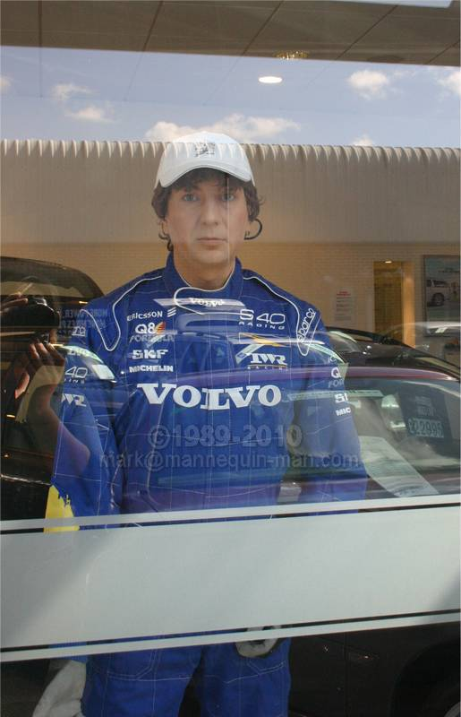 human mannequin mannequin-man in dressed in Volvo racing suit in car showroom window in Croydon. Living Mannequin Used Car Week Croydon